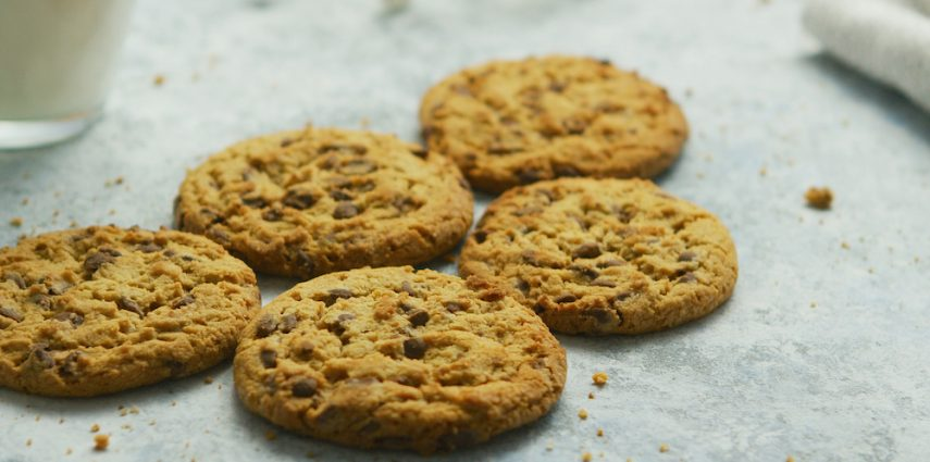 Closeup shot of sweet crunchy chocolate chip cookies lying on table with crumbles around